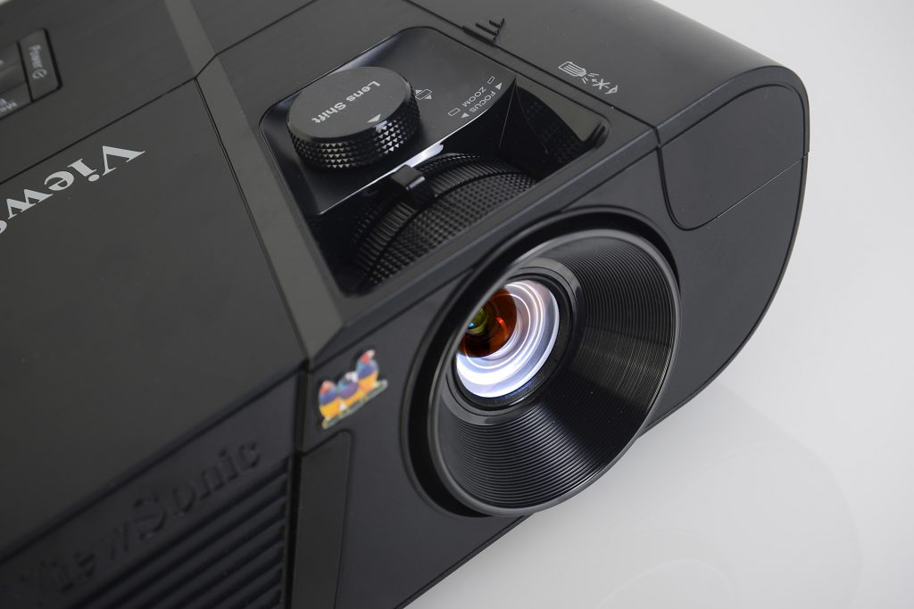Der große, runde Lens-Shift-Regler erlaubt eine präzise Höhenverstellung des Bildes auf der Leinwand. Davor befinden sich die Zoom- und Fokus-Regelungen. Damit lassen sich die Bildgröße und die Schärfe haargenau einstellen. Rechts daneben ist die Klappe für den WLAN-Dongle. Vollkommen unsichtbar verrichtet dieser darunter seine Tätigkeit. Foto: Michael B. Rehders
