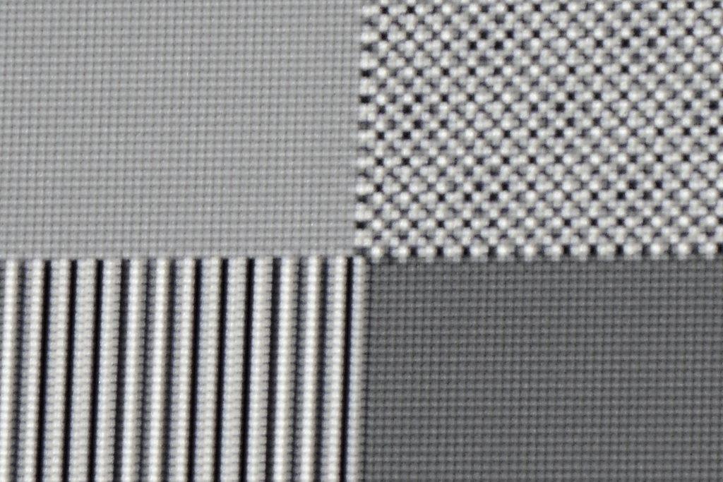 """4K-Pixelauflösung: Als nächstes wird ein Schachbrett-Testbild mit einer Auflösung von 3840 x 2160 Pixel zugespielt. Oben links ist jeder einzelne Pixel klar und deutlich abgegrenzt. Allerdings erscheint die gesamte Fläche hellgrau eingefärbt, weil sich durch die eShift-Funktion die schwarzen und weißen Pixel überlagern. Die Folge ist die """"Mischfarbe"""" Grau. Rechts daneben ist das Schachbrettmuster mit Full-HD-Auflösung zu sehen. Auch hier werden einzelne Pixel des Schachbrettmusters nicht ordentlich dargestellt. Die Ursache liegt hier ebenfalls in der eShift-Technik begründet und der """"krummen"""" Anzahl der Pixel auf dem DMD. Das Quellsignal lässt sich von 1920 x 1080 Pixel halt nicht gleichmäßig ohne zu """"interpolieren"""" auf die 2716 x 1528 Pixel hochskalieren."""