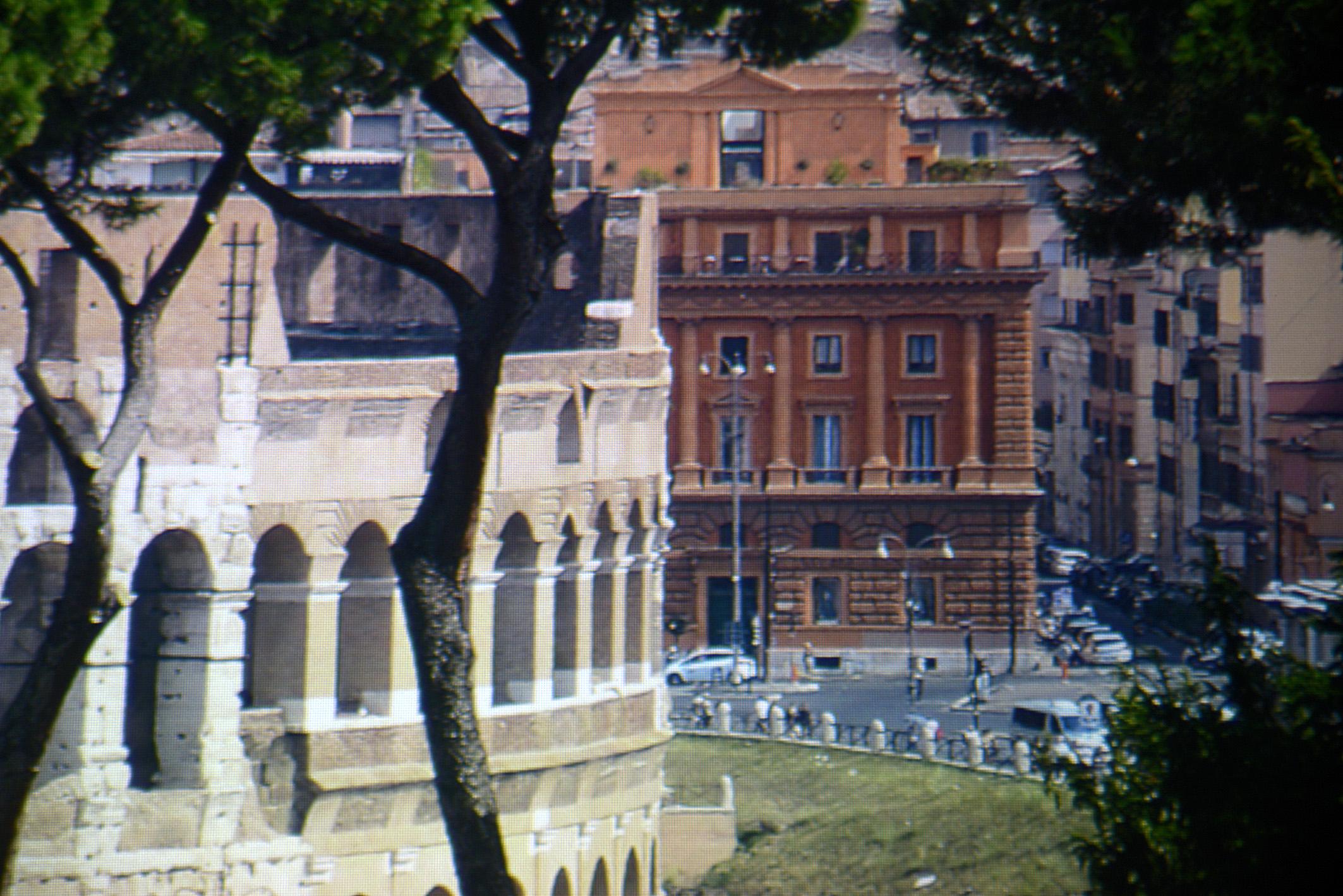 Foto: Michael B. Rehders - Dieser Screenshot zeigt einen kleinen Ausschnitt aus einem 4K-Bildwerk aus Rom. Neben dem Kolosseum steht ein gemauertes Haus in verschiedenen rot/braunen Farbtönen. Die Straßenlaternen davor sind vollständig zu sehen. Selbst der Zaun wird detailreich reproduziert, der das Kolosseum von der Straße abgrenzt.