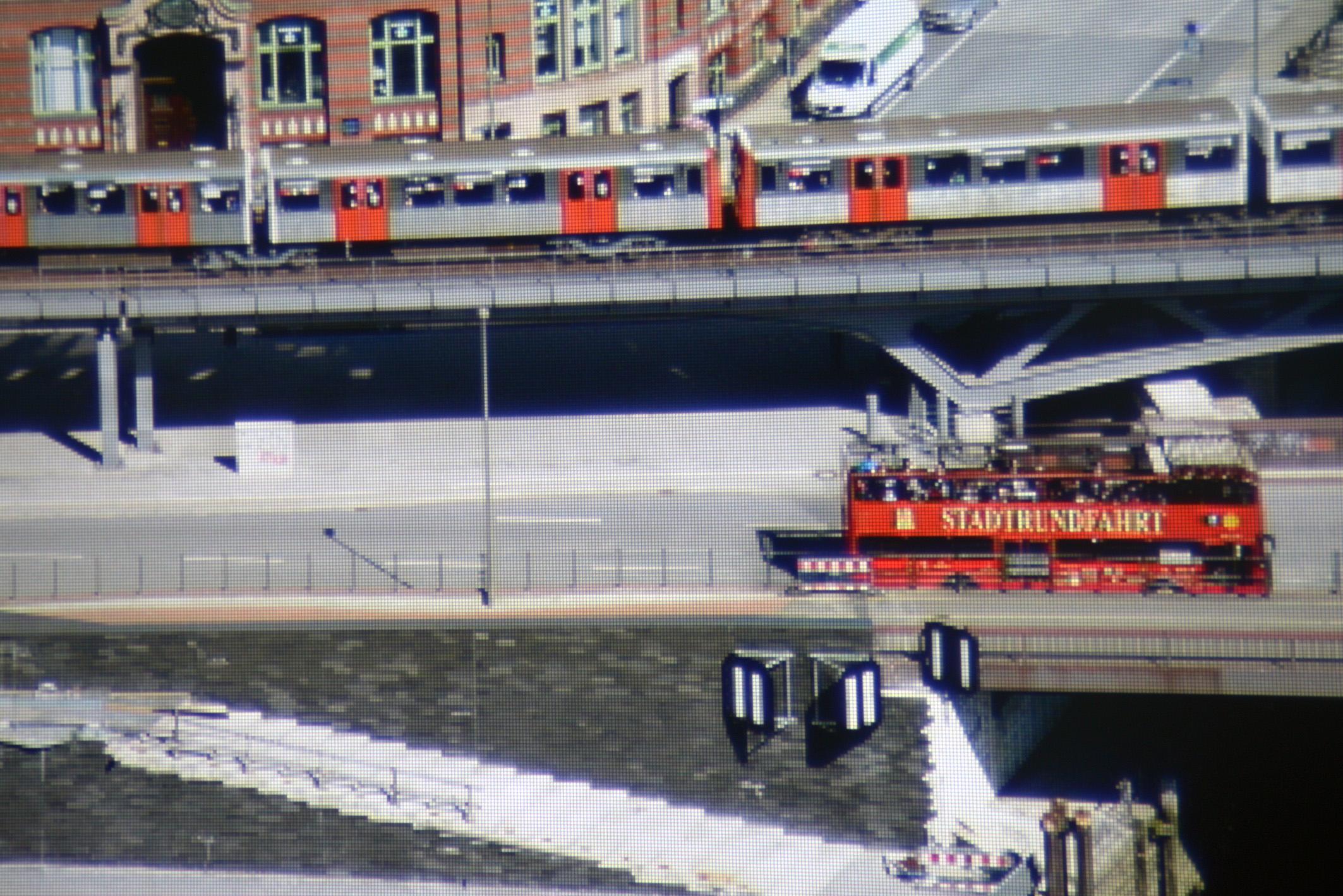 """Foto: Michael B. Rehders - Der kleine Ausschnitt aus dem projizierten Hamburg-Panorama, das ich aus der 21. Etage des Hanseatic Trade Centers geschossen habe, wird nach der Kalibrierung originalgetreu projiziert. Die orangefarbenen Türen der U-Bahn, das Rot des Doppeldeckers und der graue Asphalt gelingen ohne Fehl und Tadel. Der Schriftzug """"STADTRUNDFAHRT"""" ist gut zu lesen. Die Zeichnung dunkler Bereiche unter der Brücke ist vollständig erhalten."""