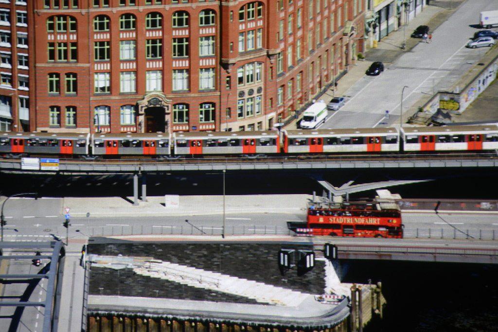 """Die Ausschnittsvergrößerung der projizierten Panoramaaufnahme deckt auf, dass die Farben exakt der Vorlage entsprechen. Der goldene Schriftzug """"STADTRUNDFAHRT"""" auf dem Doppeldecker wird ebenso original wiedergegeben wie die orangefarbenen Türen der Hamburger U-Bahn und der graue Straßenbelag."""