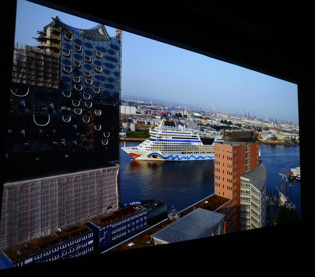"""2K-Bildwerk vom Hamburger Hafen: Die großen runden Öffnungen in der Elbphilharmonie verlieren ihre kleinen Fenster. Das Wasser vor der """"Aida sol"""" glänzt sichtbar weniger. Und es fehlen schlicht und ergreifend Mauersteine in dem orangefarbenen Hochhaus vor dem Kreuzfahrtschiff."""