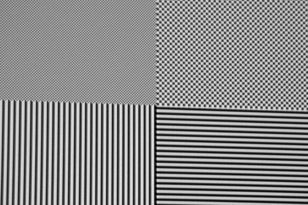 Vollkommen verfärbungsfrei und mit voller Auflösung werden selbst einzelne Pixel in Full-HD-Auflösung (oben links) des Schachbrettmusters abgebildet. Dank des hervorragenden ANSI-Kontrastwertes von 573:1 sind nur minimalste und allenfalls aus nächster Nähe sichtbare Überstrahlungen zu erahnen, die in der Praxis aber mal so gar keine Rolle spielen.