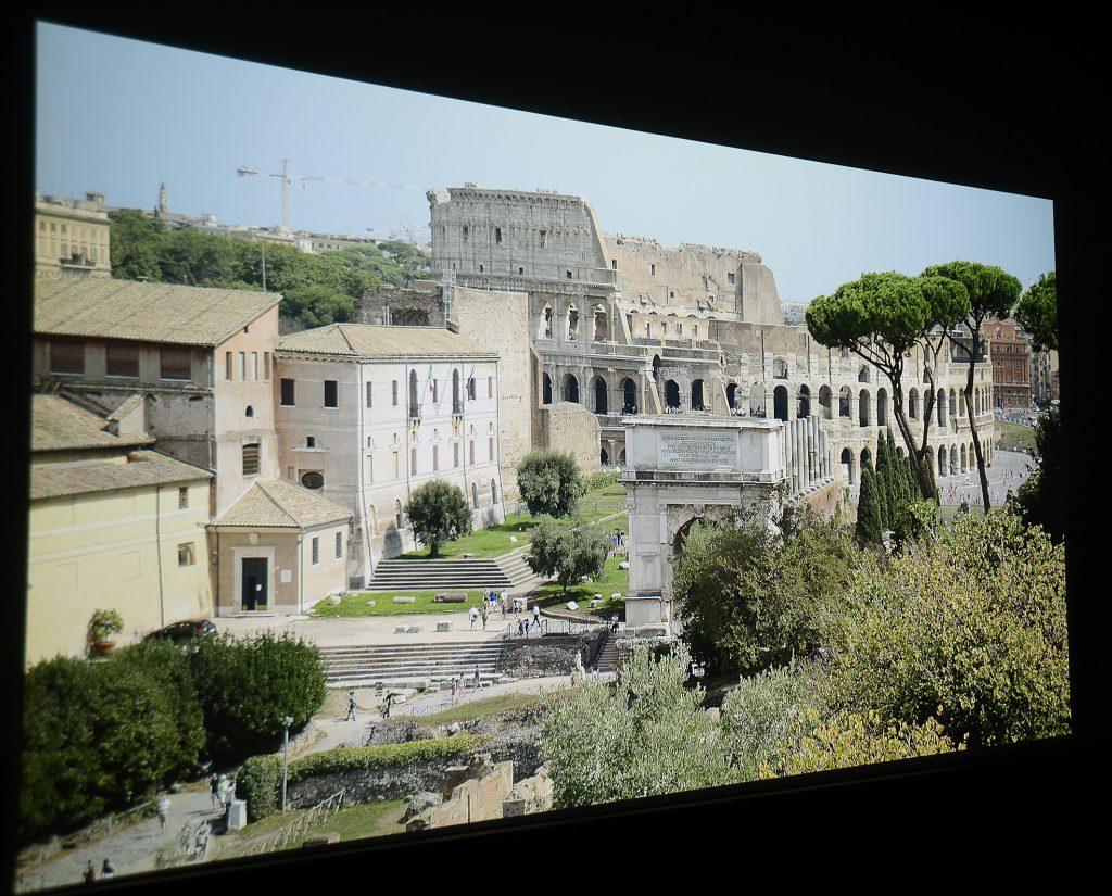 Dieser Projektor macht mir so viel Spaß, dass ich gleich noch ein neues Bildwerk zuspiele, das ich vor wenigen Wochen in Rom geschossen habe. Es zeigt im Hintergrund das Kolosseum, rechts daneben ein rotes gemauertes Gebäude und verschiedenste Grünfarbtöne.