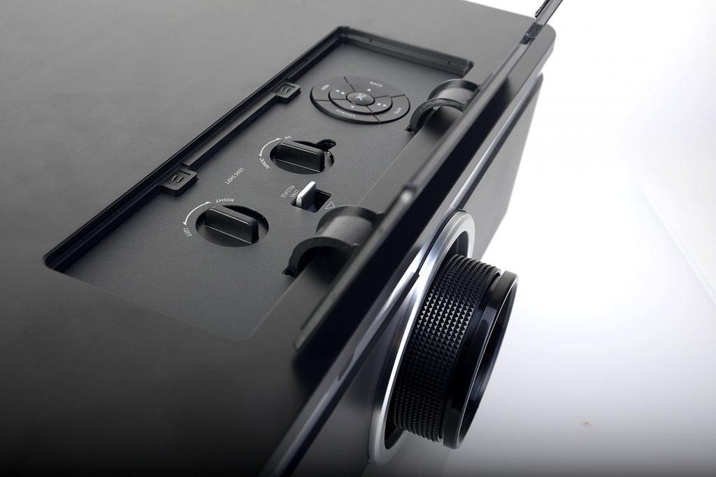 Zwischen den Drehknöpfen für den horizontalen/vertikalen Lens-Shift befindet sich die Entriegelung für das Objektiv. Ganz sind die Tasten zu sehen für sämtliche Menüeinstellungen, falls die Fernbedienung mal nicht zur Hand sein sollte. Foto: Michael B. Rehders