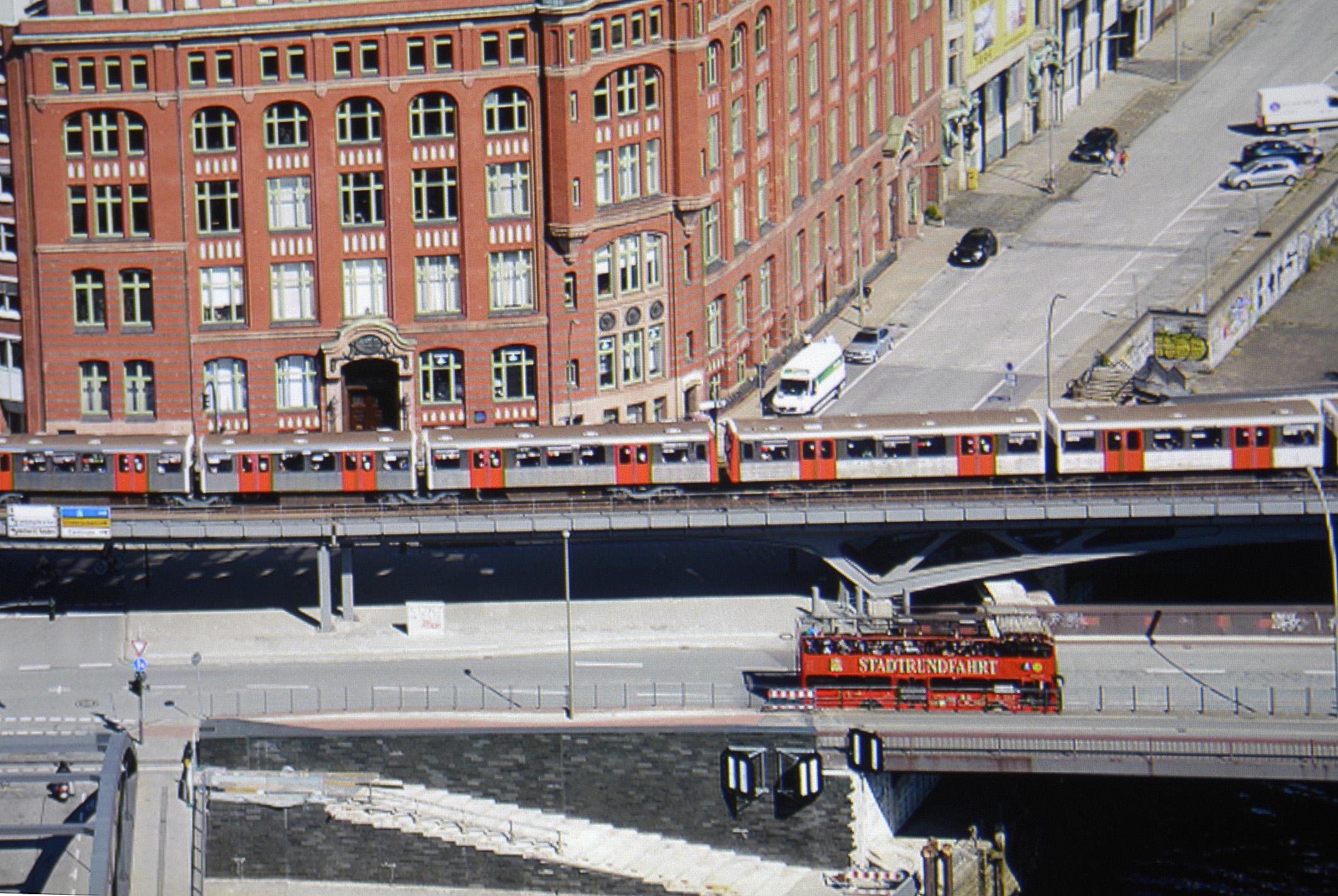 Foto: Michael B. Rehders - Auf den ersten Blick ist auf der ca. 1-%-Ausschnittsvergrößerung des Screenshots zu erkennen, dass der Schriftzug STADTRUNDFAHRT auf dem roten Doppeldecker vollständig lesbar ist. Das Wappen von Hamburg ist daneben komplett abgebildet. Der graue Asphalt und die orangen Türen der U-Bahn sehen natürlich aus. Letztendlich ist der dunkle Bereich unter der Brücke perfekt durchgezeichnet. Alle sichtbaren Inhalte sind vorhanden.