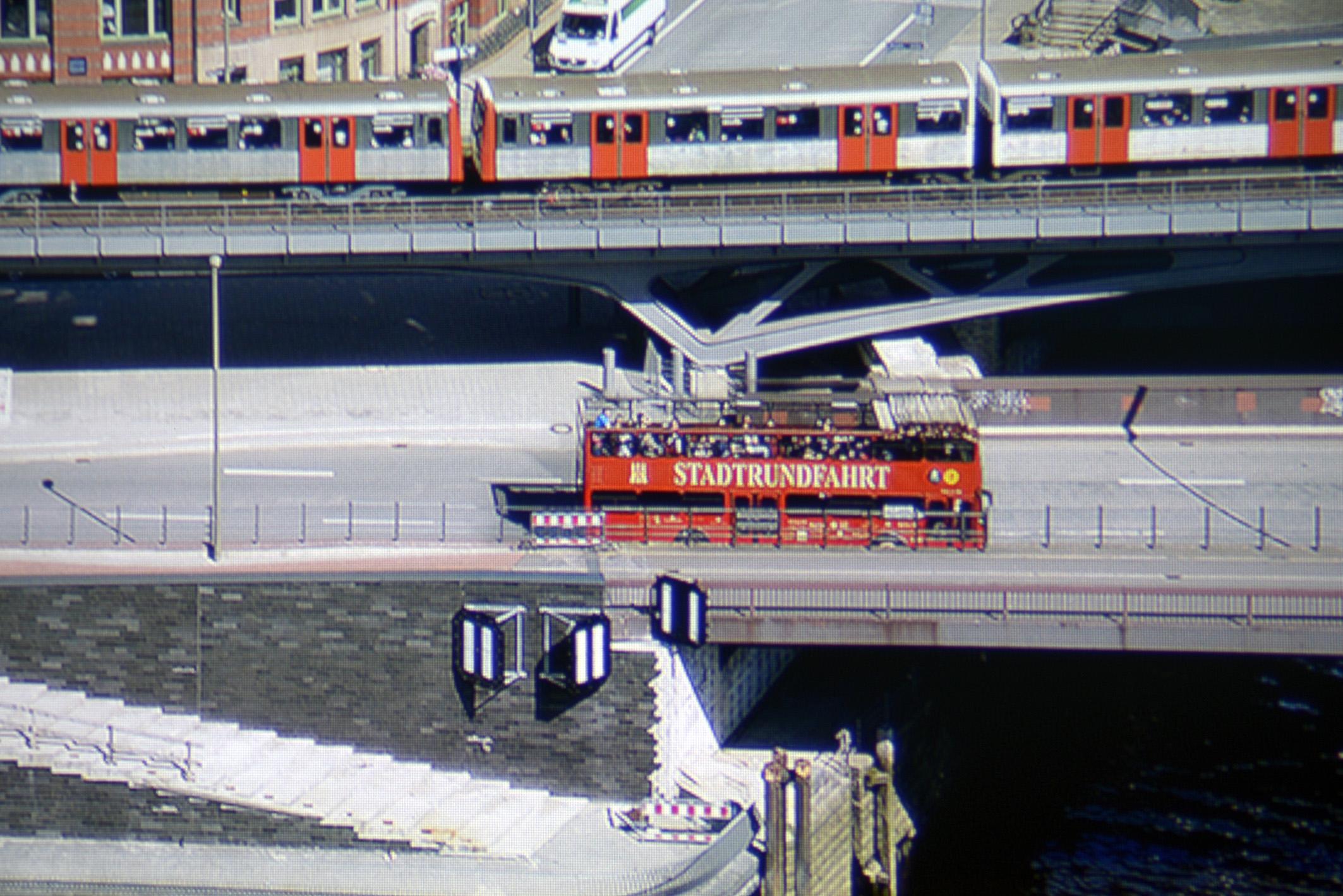 """Der Schriftzug """"STADTRUNDFAHRT"""" wird vollständig reproduziert, wie in der Ausschnittsvergrößerung der Panoramaaufnahme zu sehen ist. Der Asphalt erscheint farbneutral und die U-Bahn-Türen sehen originalgetreu Orange aus. Zudem sind alle Treppenstufen verfärbungsfrei zu sehen."""