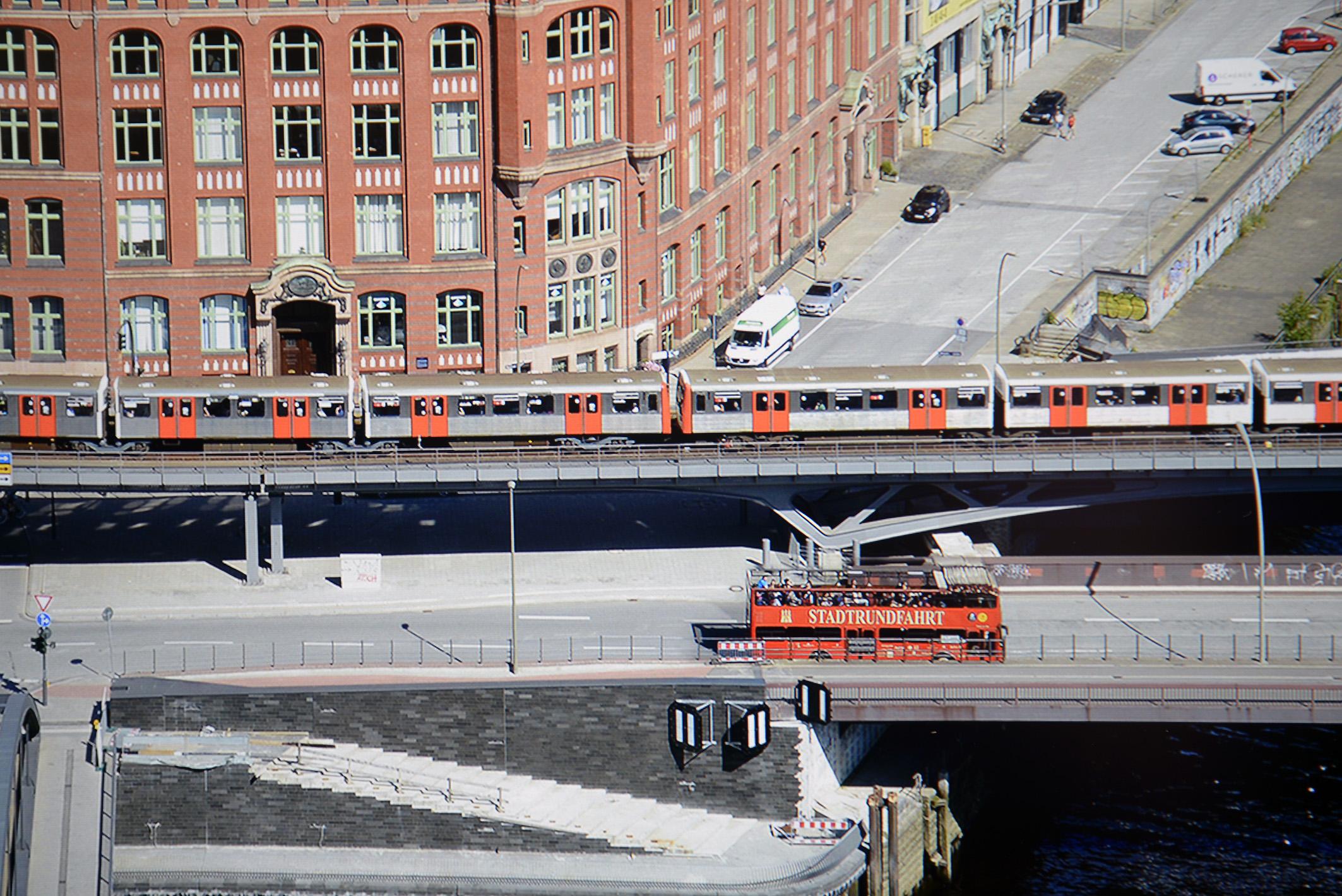 """Diese Panoramaaufnahme von Hamburg habe ich aus der 21. Etage des Hanseatic Trade Centers geschossen. Zu sehen ist eine etwa fünf Prozent große Ausschnittsvergrößerung des Bildwerkes auf dem SW271, auffallend gut gelingt die rote Farbdarstellung. Der rote Doppeldecker mit dem goldenen Schriftzug """"STADTRUNDFAHRT"""", die orangenen U-Bahntüren und das Backsteingebäude im Hintergrund werden originalgetreu reproduziert. Die Darstellung der Straße zeigt den grauen Asphalt und sämtliche Steine perfekt, auch die weiße Treppe zum Wasser ist klar und deutlich erkennbar. Foto: Michael B. Rehders"""