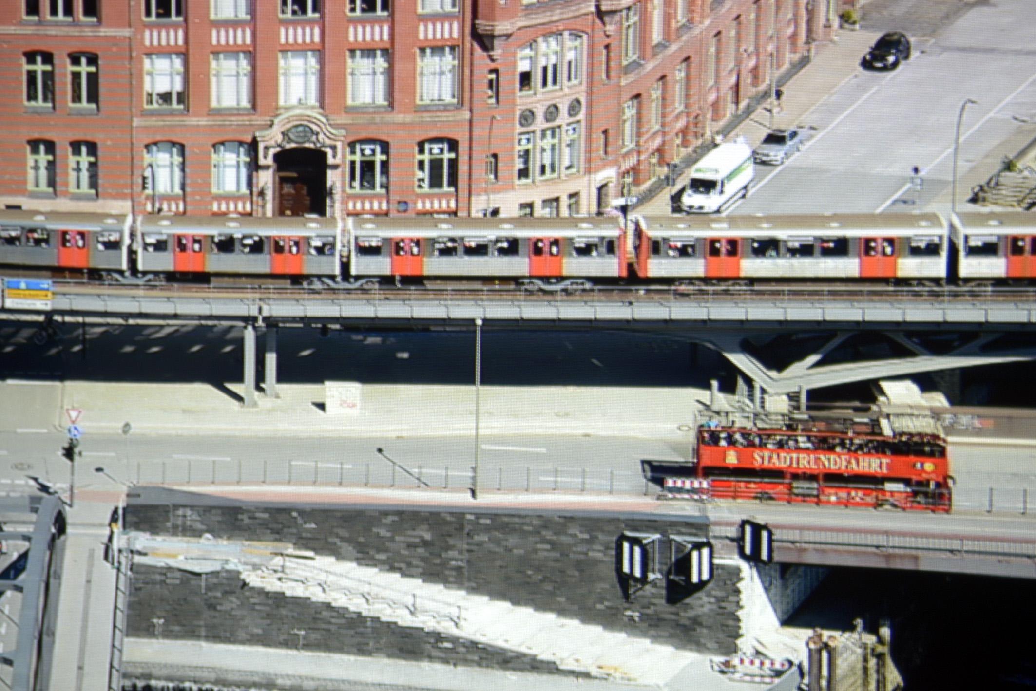"""Foto: Michael B. Rehders Full-HD: Die Panoramaaufnahme von Hamburg habe ich aus der 21. Etage des Hanseatic Trade Centers geschossen. Der Ausschnitt aus dem projizierten Full-HD-Bildes zeigt eine ordentliche Farbdarstellung. Der Schriftzug """"STADTRUNDFAHRT"""" ist gut zu lesen. Der Asphalt erscheint angenehm farbneutral."""