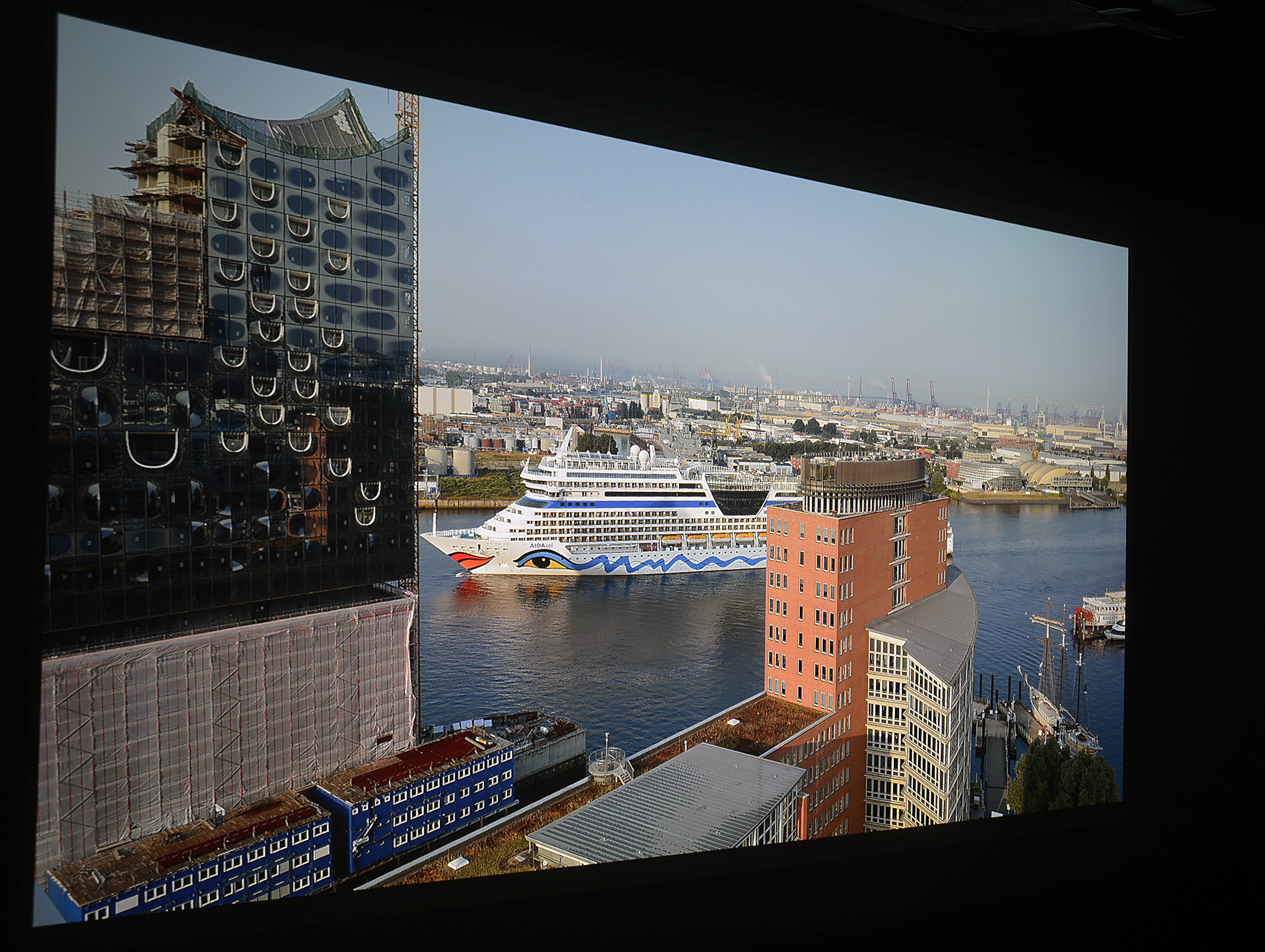 """Foto: Michael B. Rehders Das in UHD-Auflösung zugespielte Foto vom Hamburger Hafen, auf dem die """"Aida Sol"""" die Elbe hinauf fährt, wird ein wenig kontrastarm dargestellt. Ein Helligkeitsabfall zu den Seiten ist im Grunde kaum auffällig. Dafür sehen die Farben natürlich aus. Umwerfend ist darüber hinaus die Schärfe. Feinste Details sind erkennbar."""