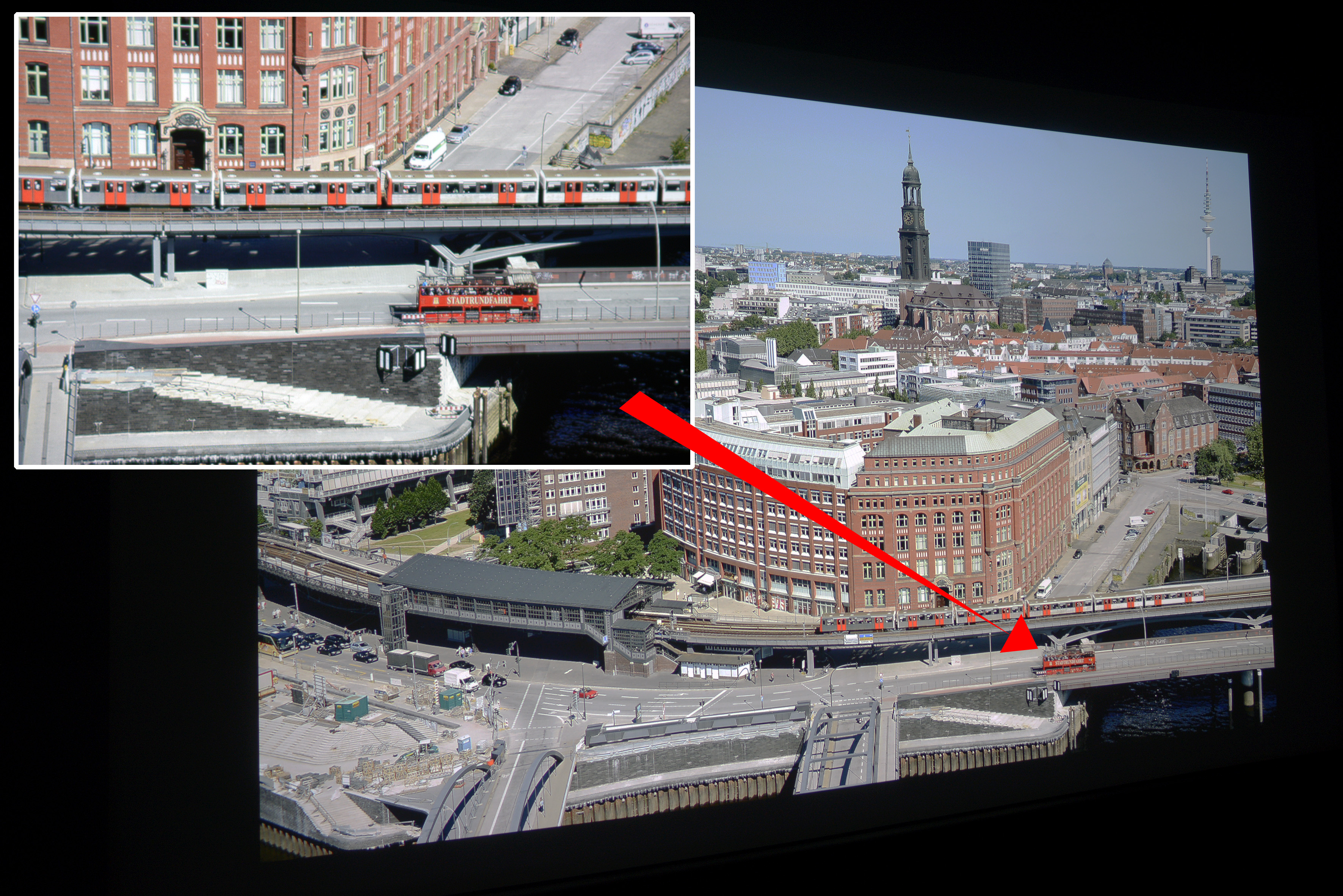 """Foto: Michael B. Rehders Das Hamburg Panorama habe ich aus der 21. Etage des Hanseatic Trade Centers geschossen. Auf dem Foto werden die Farben originalgetreu reproduziert. Der leichte Blauverlauf im Himmel gelingt dem W1700 übergangslos mit allen Nuancen. In der Ausschnittsvergrößerung (oben links) wird deutlich, wie hervorragend die Schärfe dieser UHD-Auflösung projiziert wird. Der Schriftzug """"STADTRUNDFAHRT"""" wird vollständig auf dem roten Doppeldecke abgebildet. Der Asphalt ist farbneutral und die orangenen U-Bahntüren realistisch."""