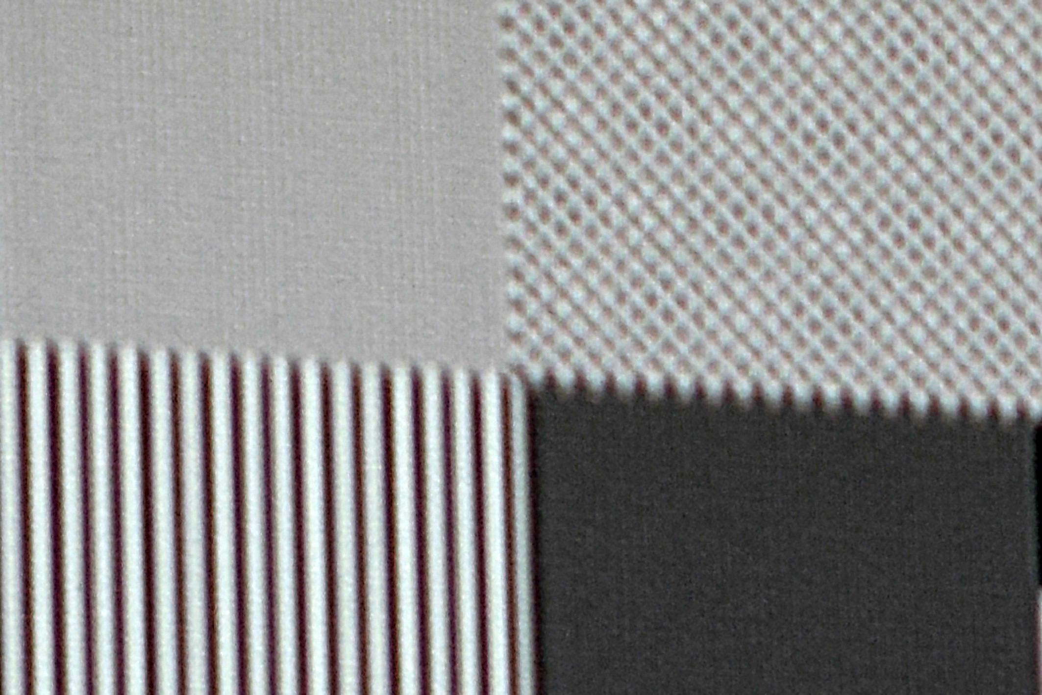 """4K-Pixelauflösung: Als nächstes wird ein Schachbrett-Testbild mit einer Auflösung von 3840 x 2160 Pixel zugespielt. Oben links ist jeder einzelne Pixel klar und deutlich abgegrenzt. Allerdings erscheint die gesamte Fläche hellgrau eingefärbt, weil sich durch die Shift-Funktion die schwarzen und weißen Pixel überlagern. Die Folge ist die """"Mischfarbe"""" Grau. Rechts daneben ist das Schachbrettmuster mit Full-HD-Auflösung zu sehen. Auch hier werden einzelne Pixel des Schachbrettmusters nicht ordentlich dargestellt. Die Ursache liegt hier ebenfalls in der XPR-Shift-Technik begründet und der """"krummen"""" Anzahl der Pixel auf dem DMD. Das Quellsignal lässt sich von 1920 x 1080 Pixel halt nicht gleichmäßig ohne zu """"interpolieren"""" auf die 2716 x 1528 Pixel hochskalieren."""