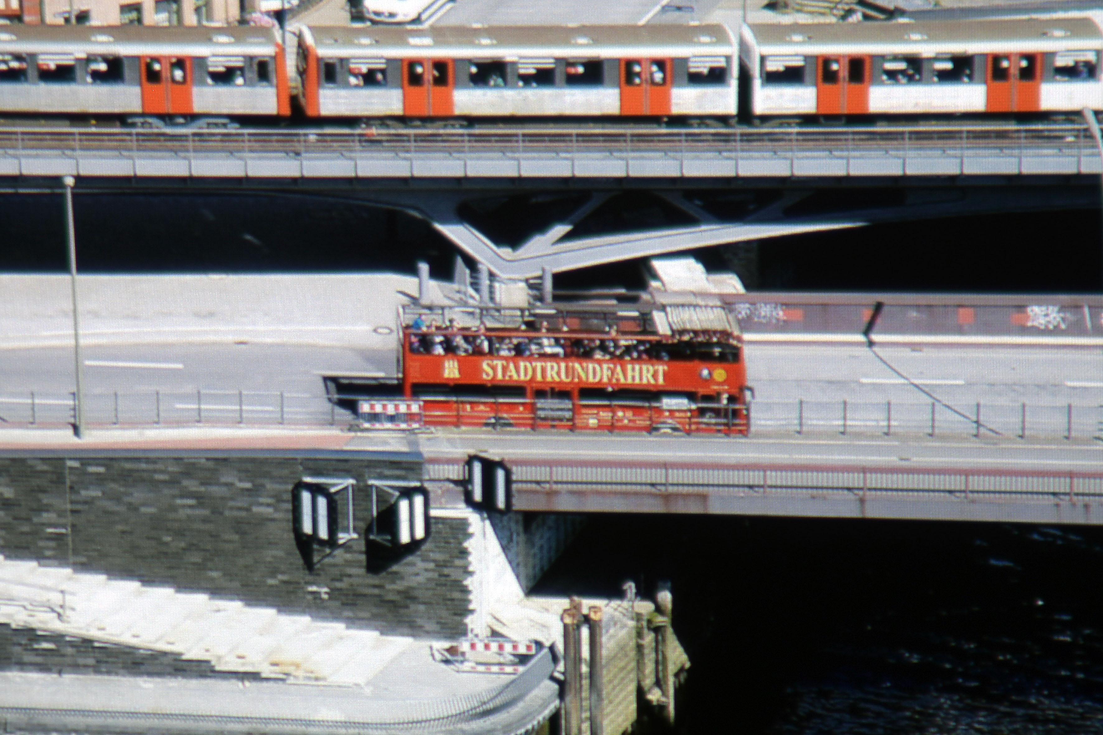 """Foto: Michael B. Rehders (Originalaufnahme) In der Ausschnittsvergrößerung des Screenshots sieht der Asphalt völlig farbneutral aus. Die orangefarbigen U-Bahntüren werden originalgetreu reproduziert. Der hellrote Doppeldecker stellt den Schriftzug """"STADTRUNDFAHRT"""" und das Wappen links daneben vollständig und farbkorrekt dar. Die Durchzeichnung gelingt dem BenQ TK800 außerordentlich gut. Unter der Brücke ist das blaue Wasser klar zu sehen."""