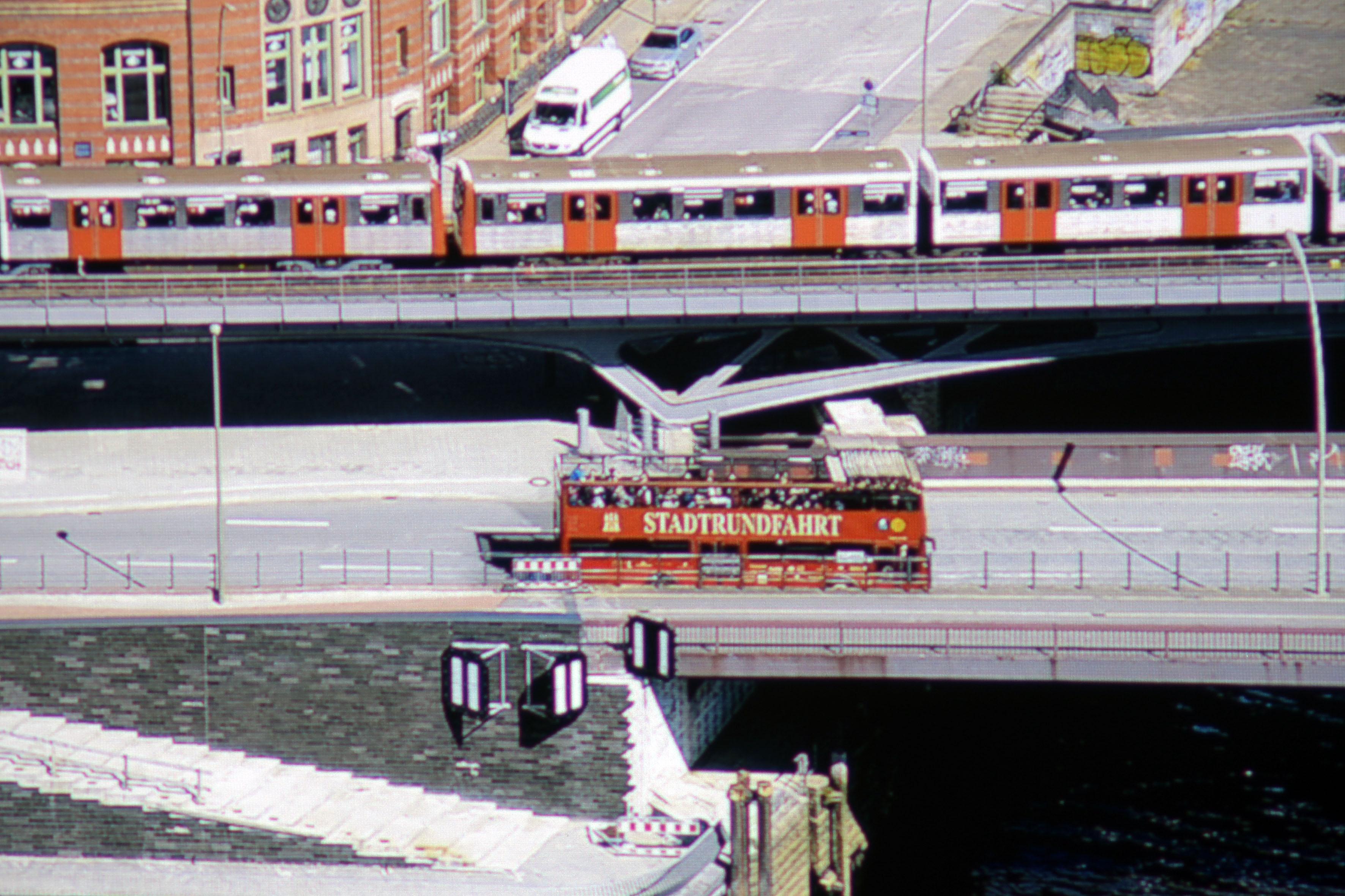 """Foto: Michael B. Rehders (Originalaufnahme) Der kleine 5 % große Ausschnitt des Screenshots deckt auf, dass der Acer H6810 den Schriftzug """"STADTRUNDFAHRT"""" und links daneben das Hamburger Wappen auf dem roten Doppeldecker vollständig darstellt. Der leichte beige Farbton wird vorzüglich reproduziert. Das Orange der U-Bahntüren sieht ebenfalls gut aus, erreicht aber nicht die Farbpräzision des Originals. Der graue Asphalt ist hingegen völlig farbneutral. Die Durchzeichnung gelingt dem Acer ebenfalls sehr gut. Unter der Brücke ist sogar das blaue Wasser zu erkennen."""