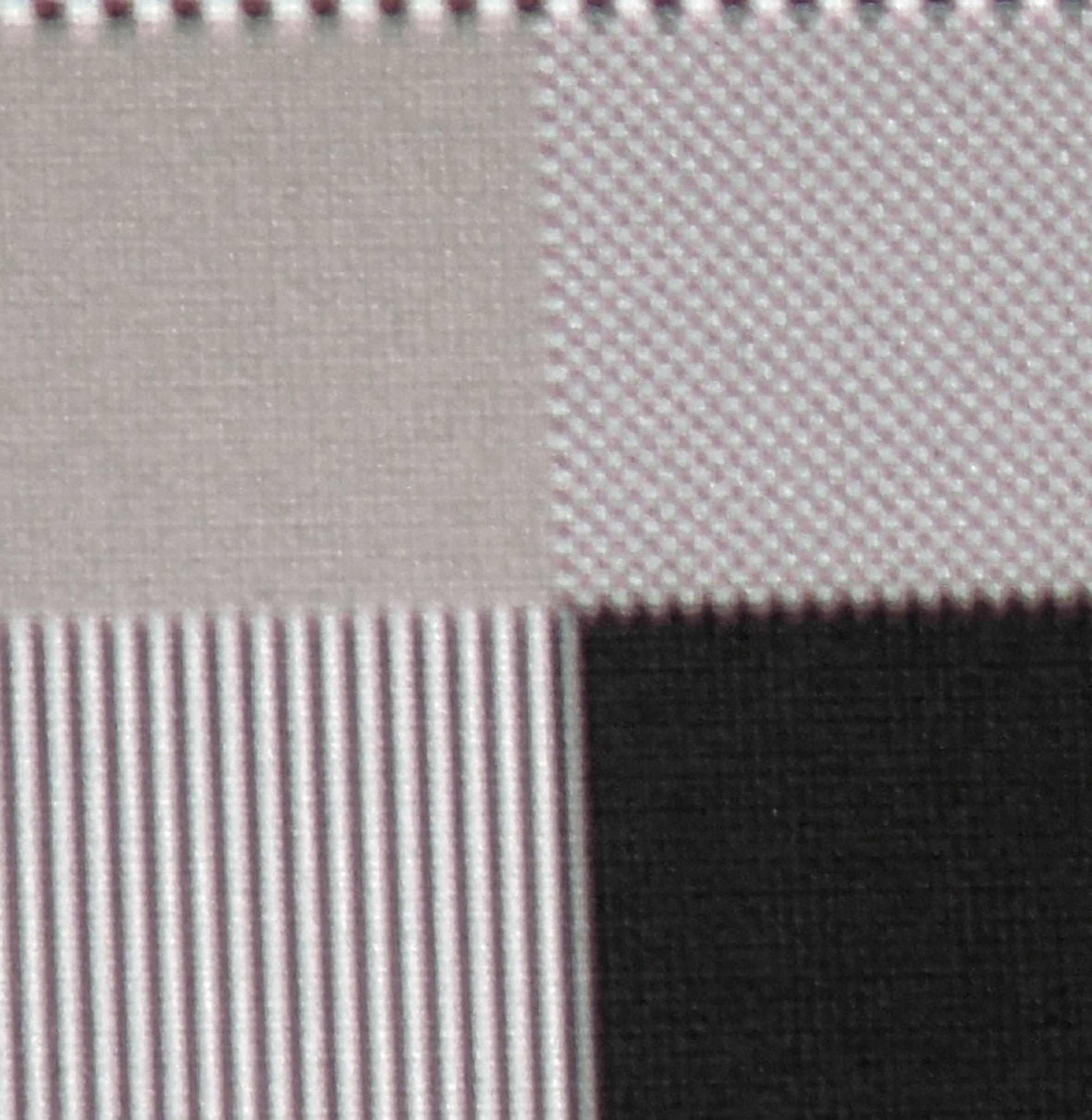 UHD-Auflösung: Diese Makroaufnahme soll (oben links) schwarze und weiße Schachbrettfelder in UHD-Auflösung offenbaren. Hier wird die Arbeitsweise von XPR-Shift ziemlich deutlich. Es sind keine einzelnen Pixel mehr erkennbar. Durch die Überlagerung entsteht eine mittelgraue Farbfläche. Oben rechts ist das Full-HD-Schachbrett hingegen gut zu differenzieren.