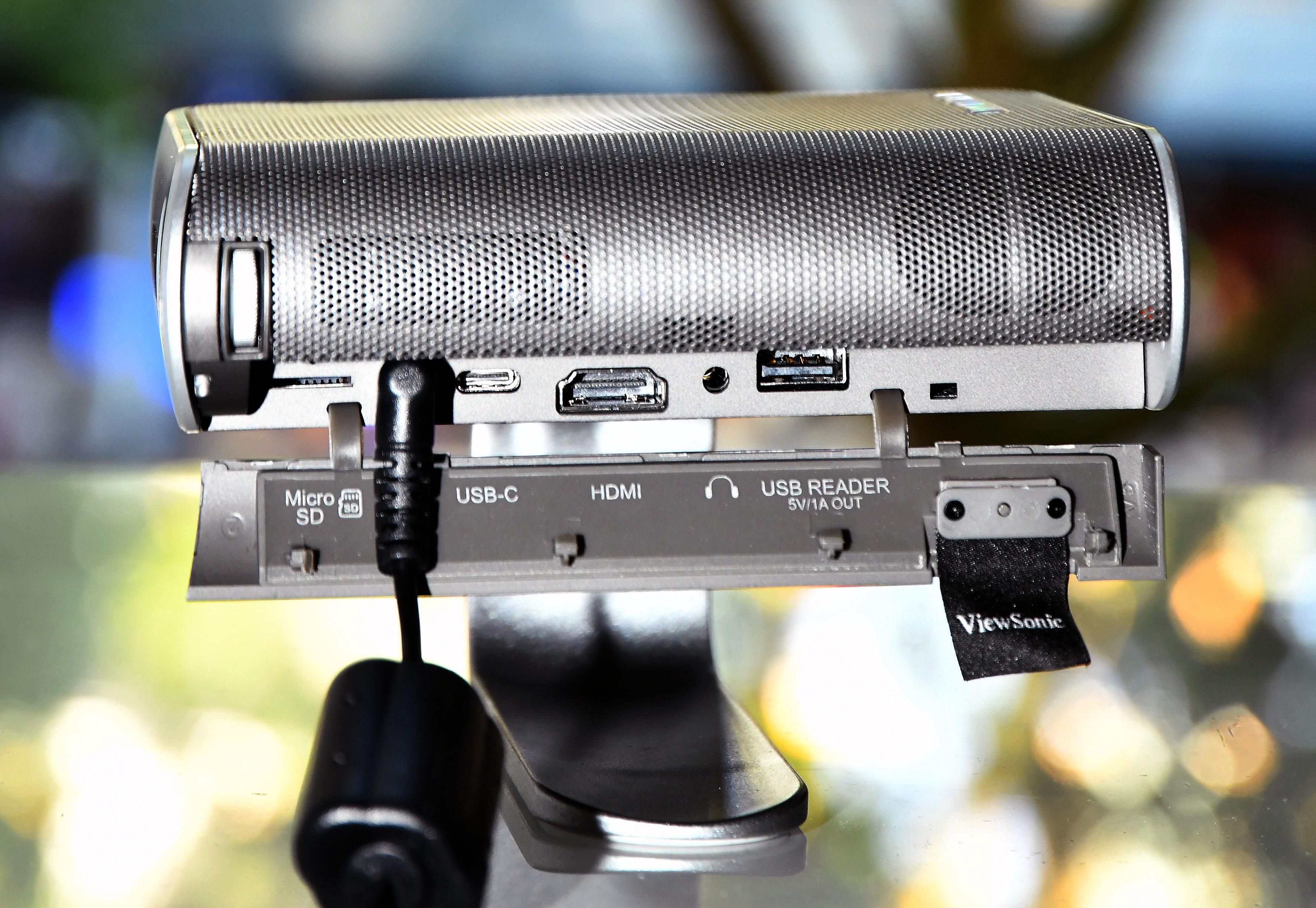 Foto: Michael B. Rehders Alle Anschlussbuchsen befinden sich unter einer seitlichen Klappe. Eine kleine Lasche aus Stoff dient als Öffner. Ein beherzter Zug daran und die Klappe springt auf. Netz- und Ladekabel gehören zum Lieferumfang. Nun können Blu-ray-Player, USB-Stick, SD-Karte, Kopfhörer und das Notebook am M1 genutzt werden.
