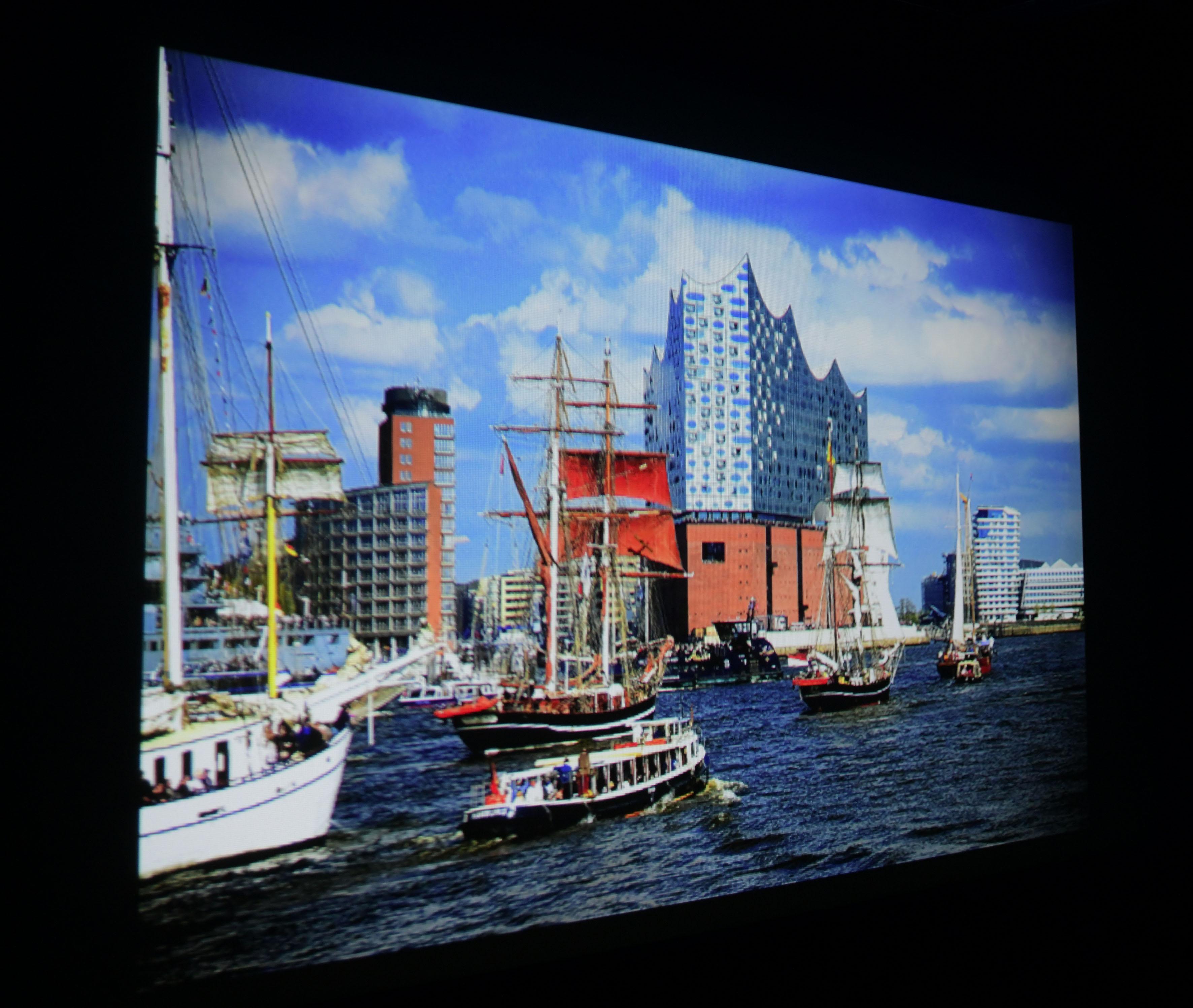 Foto: Michael B. Rehders Auf 135 cm Bildbreite in meinem Heimkino – also ganz ohne Umgebungslicht – sieht der Hamburger Hafen prachtvoll aus. Auch wenn der Himmel ob der etwas höheren Farbtemperatur minimal blauer erscheint als gewohnt, sehen die Farben bestechend realistisch aus.