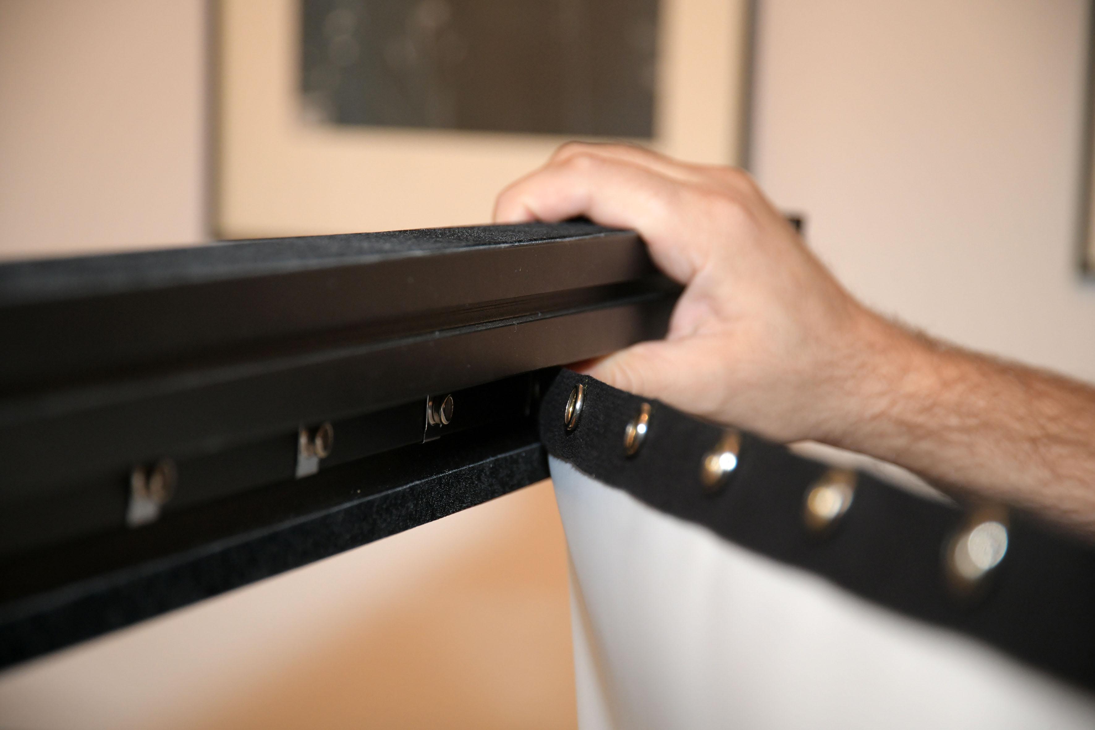 Foto: Michael B. Rehders Nun wird das Tuch Knopf für Knopf an den Rahmen befestigt. Zu meiner Überraschung gelingt spielend einfach. Obendrein ist das Tuch perfekt gespannt, obwohl die Demoleinwand bereits mehrere Dutzend Male auf- und abgebaut worden ist. Es gibt nicht eine einzige Welle. Das Tuch ist spiegelglatt gespannt. Bravo!