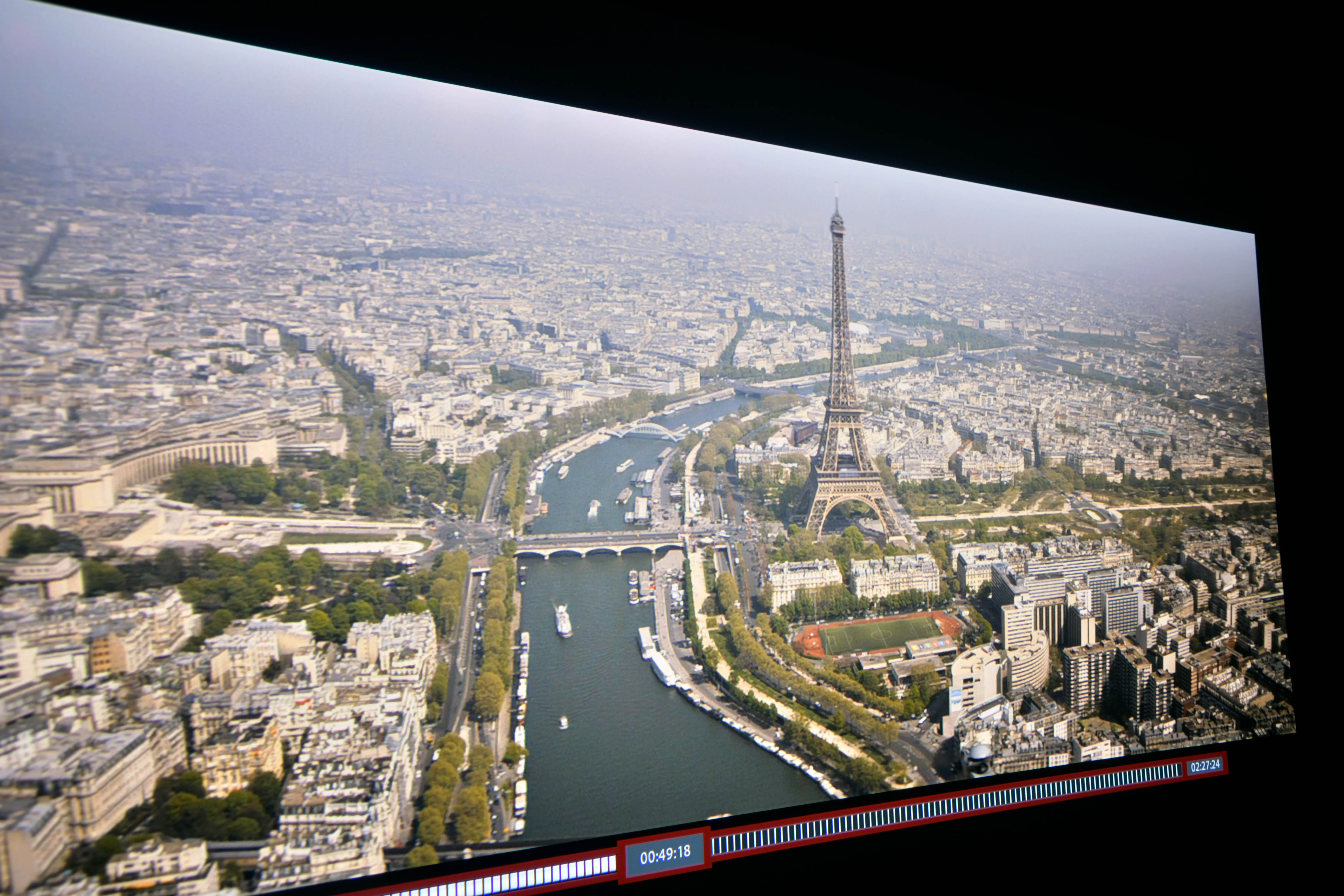 """Full HD – In MISSION IMPSSIBLE: FALLOUT zeigt die Panoramaaufnahme von Paris viele Einzelheiten. Der Eifelturm weist klare Konturen auf. Einzelne Metallstreben sind zu erkennen. Die Bäume links und rechts von der Seine sind ebenfalls klar und deutlich vorhanden. Die weiter entfernten Gebäude """"verschwimmen"""" im Schleier des diesigen Himmels."""