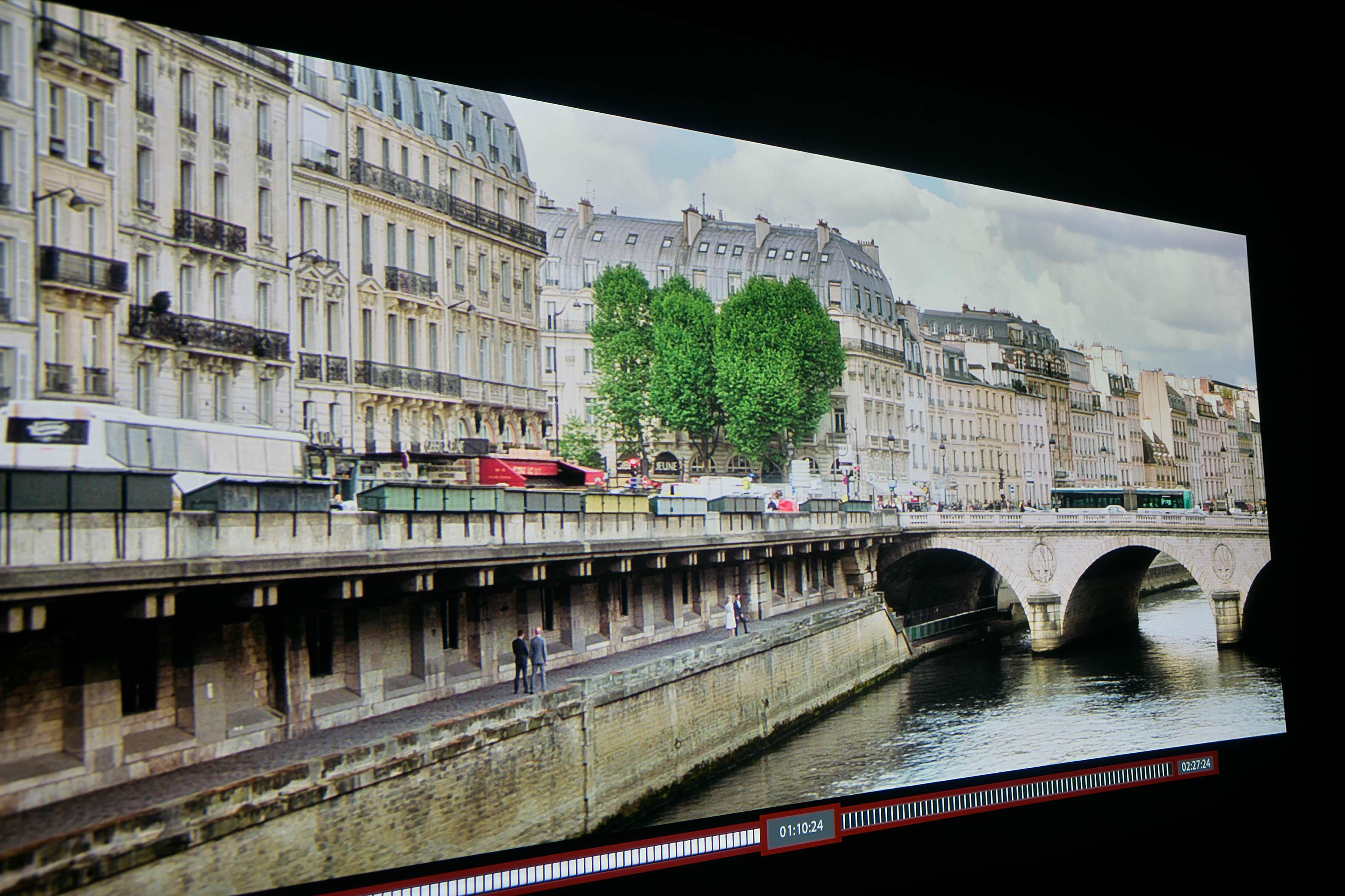 Full HD – Der Himmel über Paris ist gut durchgezeichnet. Einzelne Wolken sind zu erkennen. Die grünen Bäume im Hintergrund weisen viele Blätter auf. Die Brücke lässt eine Struktur erahnen, ebenso die Kaimauer auf der linken Seite.