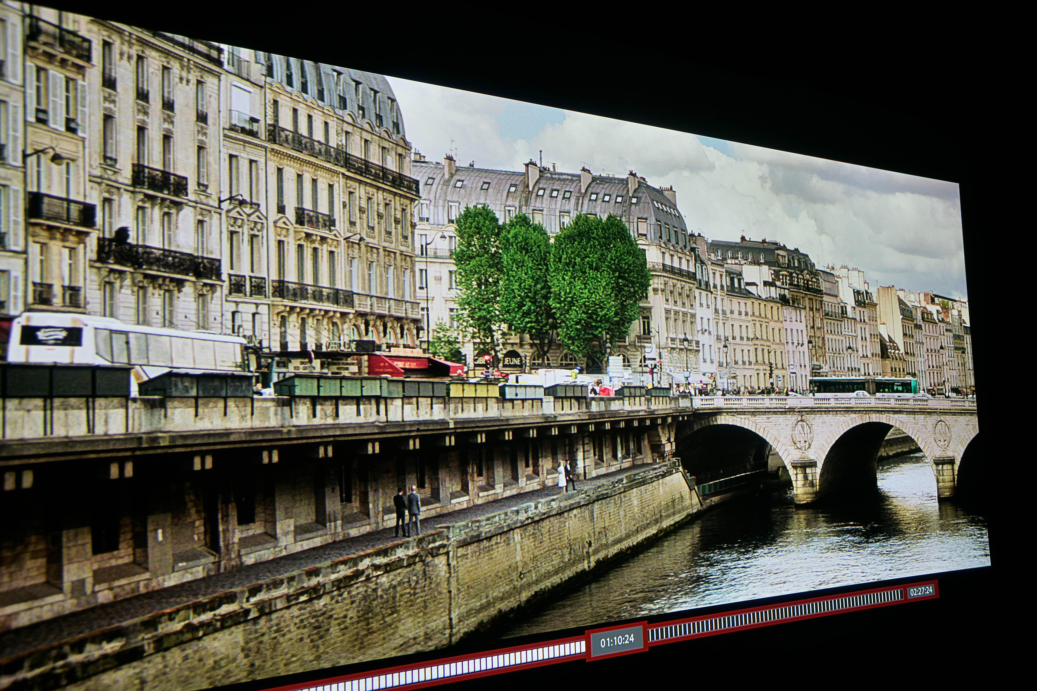 HDR – Auch in dieser Szene legt die HDR-Fassung noch eine Schippe drauf. Die Bäume besitzen noch mehr Zeichnung und ein satteres Grün. An der Brücke ist jeder einzelne Mauerstein vorhanden, ebenso an der Kaimauer. Selbst die Fenster der Gebäude profitieren erheblich von der 4-mal höheren Auflösung gegenüber der Full-HD-Fassung.