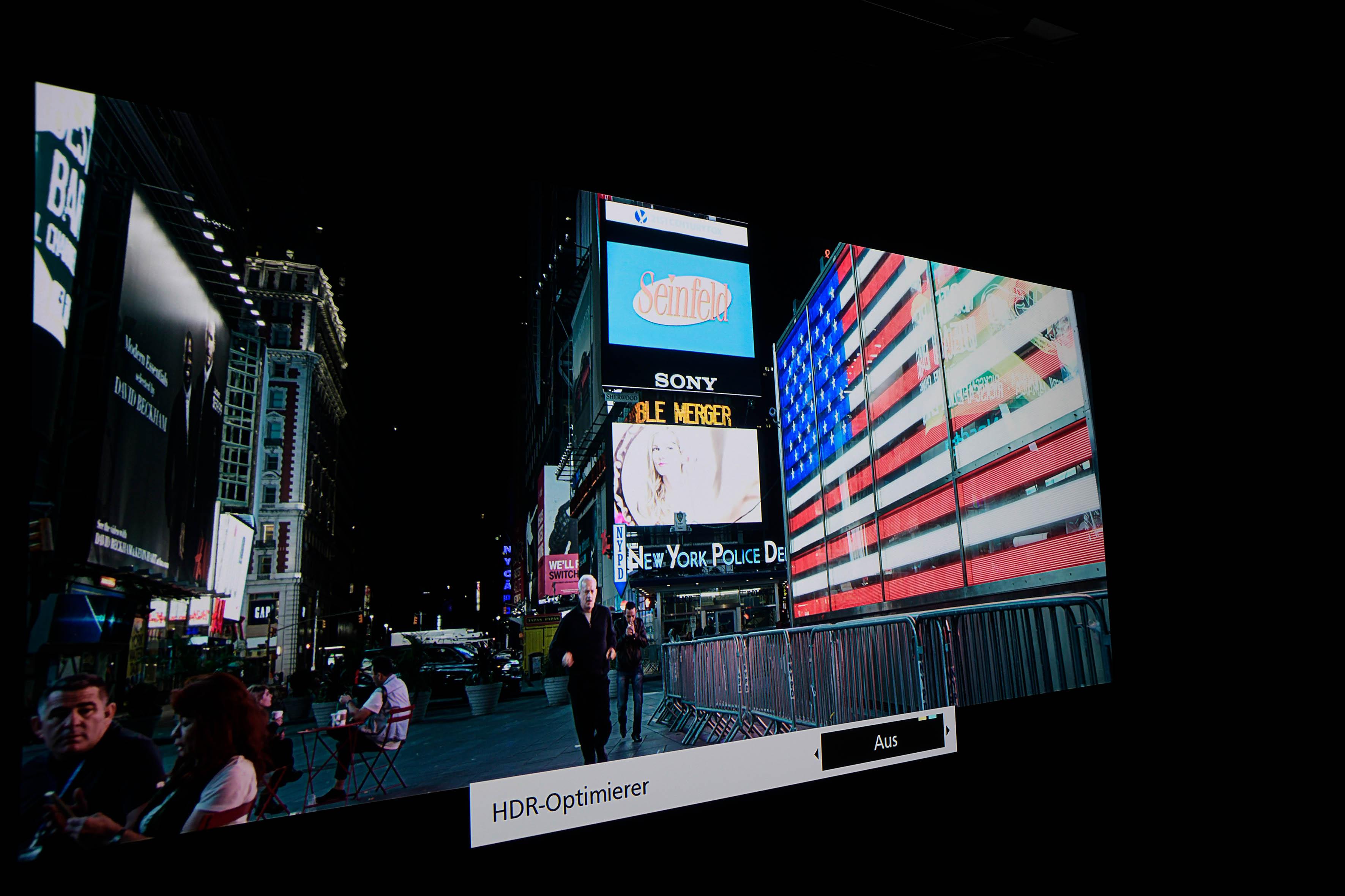HDR – SULLY ohne HDR Optimierer Als Sully nach der Landung seiner Passagiermaschine durch das nächtliche New York joggt, sind auf verschiedenen Displays zahlreiche Dinge abgebildet. Die HDR-Version zeigt diese allesamt auf. Rechts ist die US-Flagge farbenfroh zu sehen, wenn das Clipping bei 600 Nits liegt. Selbst die Frau auf dem Display hinter Sully ist noch teilweise zu sehen.