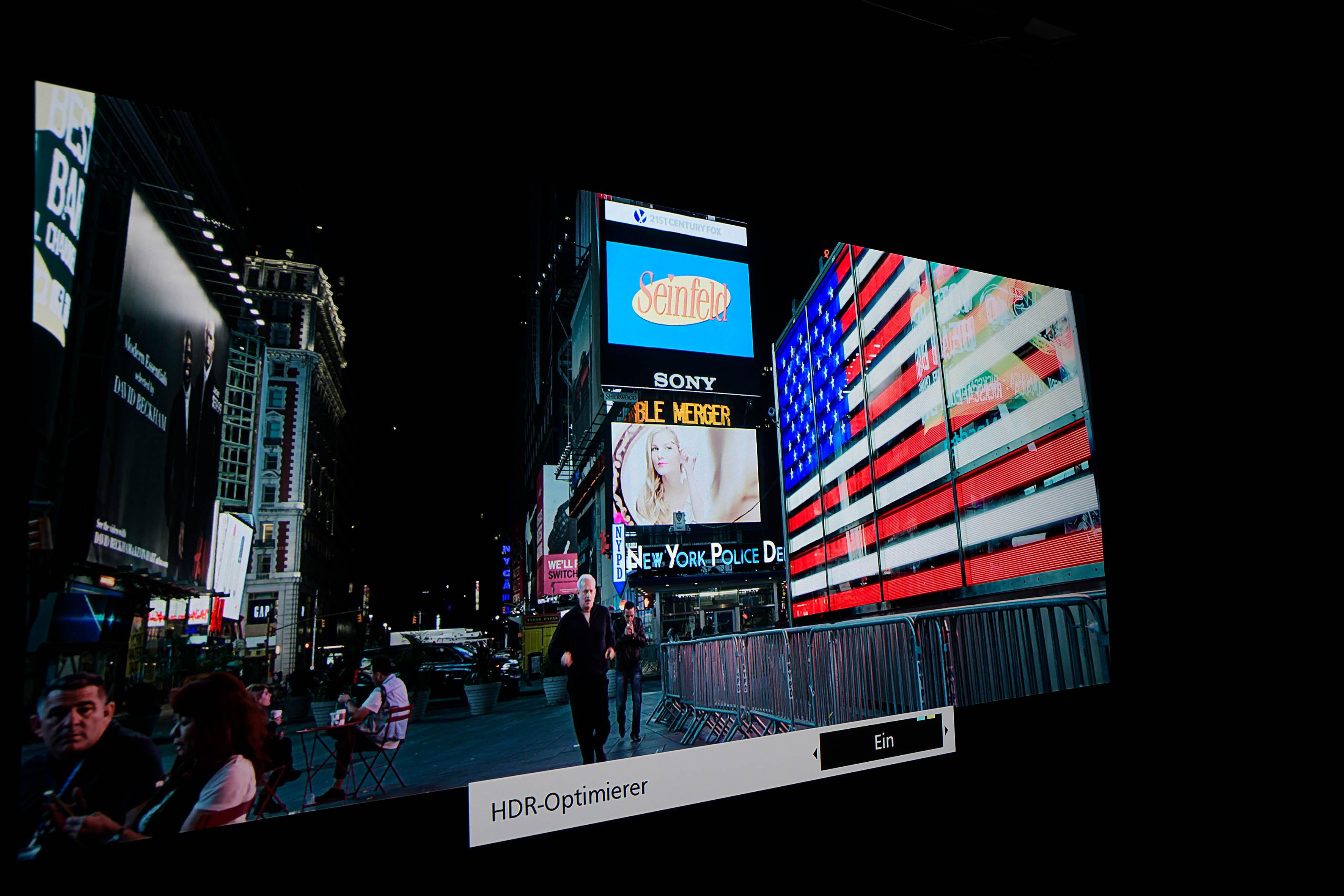 HDR – SULLY mit eingeschaltetem HDR Optimierer Auf den ersten Blick sind die Unterschiede beträchtlich. Die Frau hinter Sully auf dem Display zum Beispiel, sie ist klar und deutlich abgebildet inklusive allem Drumherum. Das Rot der US-Flagge leuchtet erheblich heller und mit noch satteren Farben. Das ist ein weiterer großer Vorteil von HDR, der meines Erachtens bislang viel zu wenig Bedeutung bekommt. Sogar das Blau profitiert von der massiv höheren Lichtausbeute, die HDR in diesem Film ermöglicht.