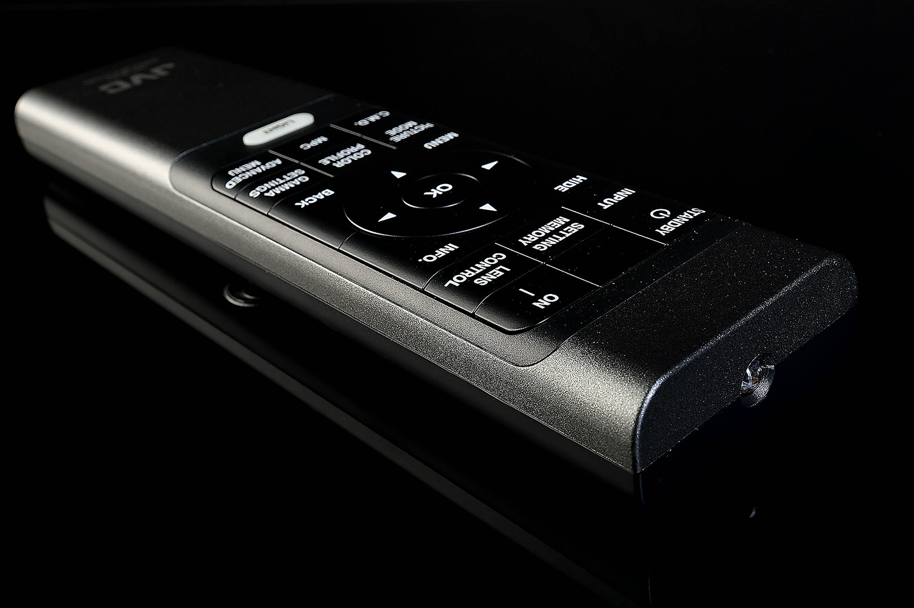 """Foto: Michael B. Rehders Die Fernbedienung des JVC DLA-X7900 sieht sehr elegant aus. Alle Tasten sind in den Handsender eingelassen. Was auf den ersten Blick wirklich schick aussieht, ist leider recht unpraktisch, denn die Tasten können nicht mehr gefühlt werden. Dank der fluoreszierenden """"Licht""""-Taste ist es jedoch möglich, die Beschriftungen zu beleuchten. Im dunklen Kino ist das wirklich hilfreich, um die gewünschten Befehle auch treffsicher auszuführen. Der neue Befehlsgeber besitzt einen """"Setting Memory""""-Knopf, mit dem alle gespeicherten Presets aufgerufen werden. Nun kann ganz bequem """"1,85:1"""" oder """"Cinemascope"""" ausgewählt werden – und der JVC DLA-N7 fährt die gewünschte Bildposition mit allen zusätzlich abgelegten Einstellungen zügig an."""