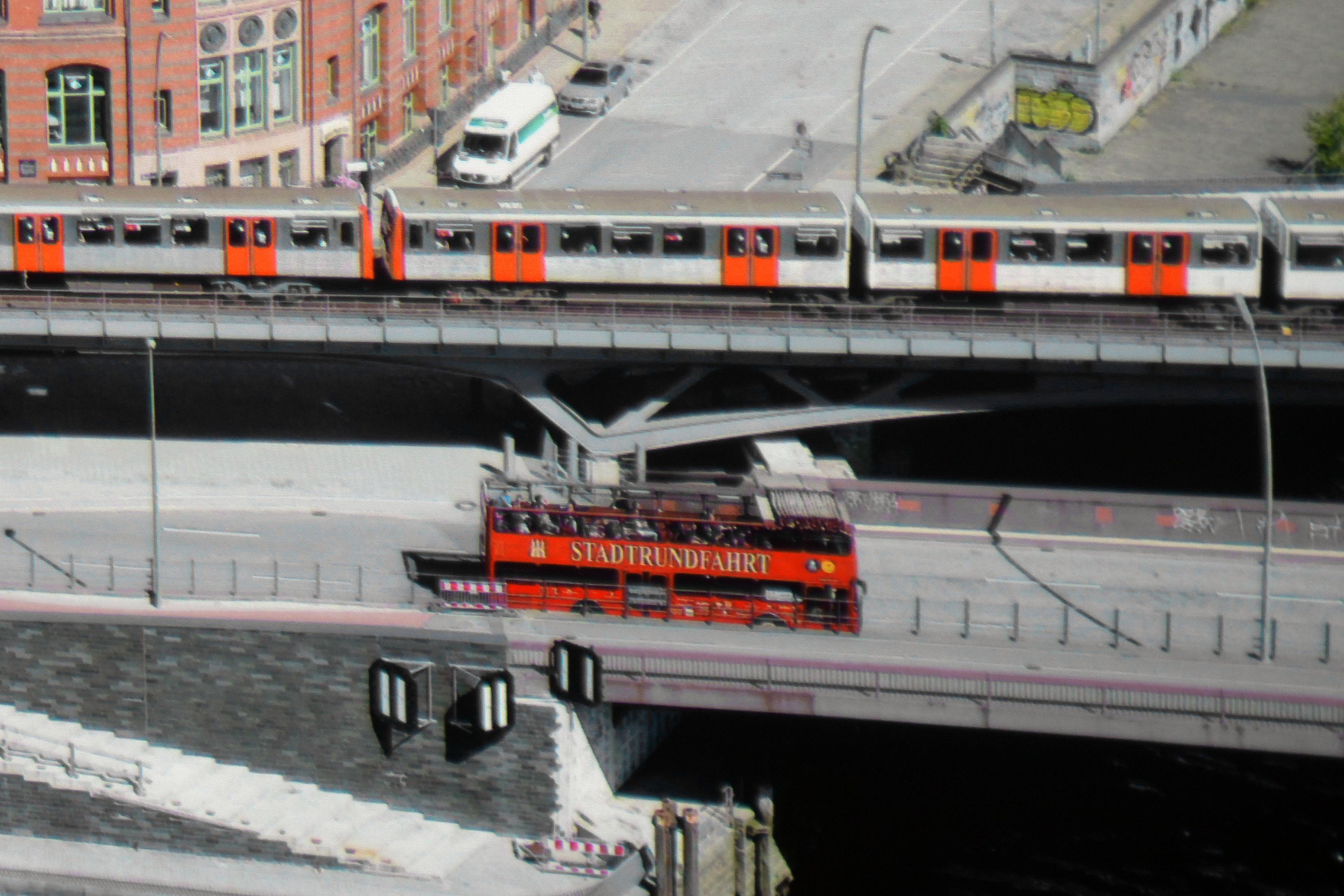 """Sony VPL-VW270 Der Schriftzug """"Stadtrundfahrt"""" ist noch klarer zu lesen. Auch das Hamburg Wappen stellt der Sony vollständig dar. Einzelne Personen im Bus sind noch deutlicher abgebildet. Allerdings führt der Sony auch eine leichte """"Unscharf Maskieren""""-Funktion durch. Um Kontrastreiche Elemente befindet sich ein dünner schwarzer Rand, der im Original so nicht vorhanden ist. Gut zu sehen am Schriftzug und den U-Bahn-Türen."""
