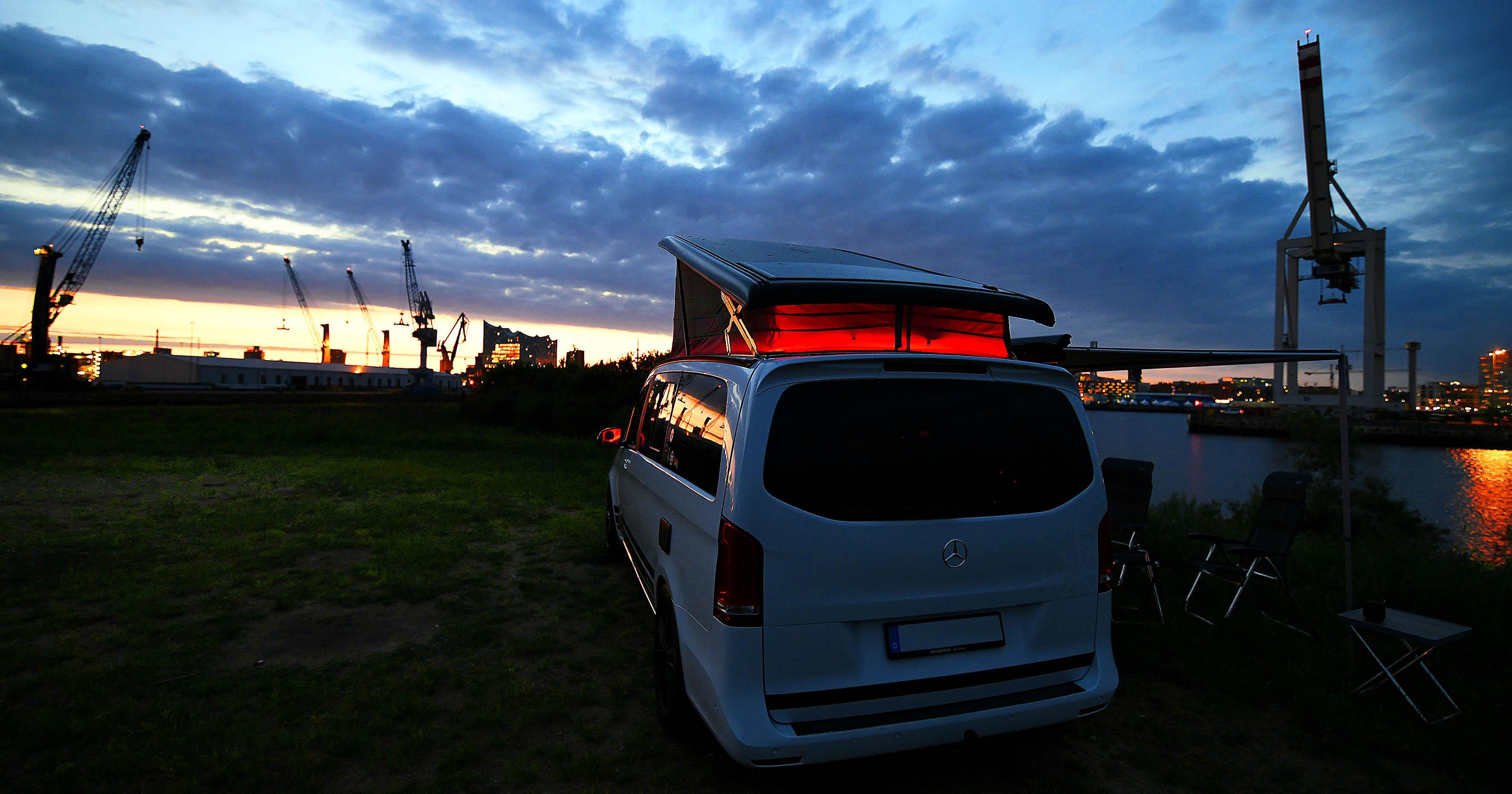 Foto: Michael B. Rehders Der Camper-Van steht direkt an der Elbe. Es ist der 21. Juni, 23.30 Uhr. Mittsommernacht. Im Hintergrund leuchtet die Elbphilharmonie vor dem Restlicht der untergehenden Sonne. Ein wirklich schöner Anblick.
