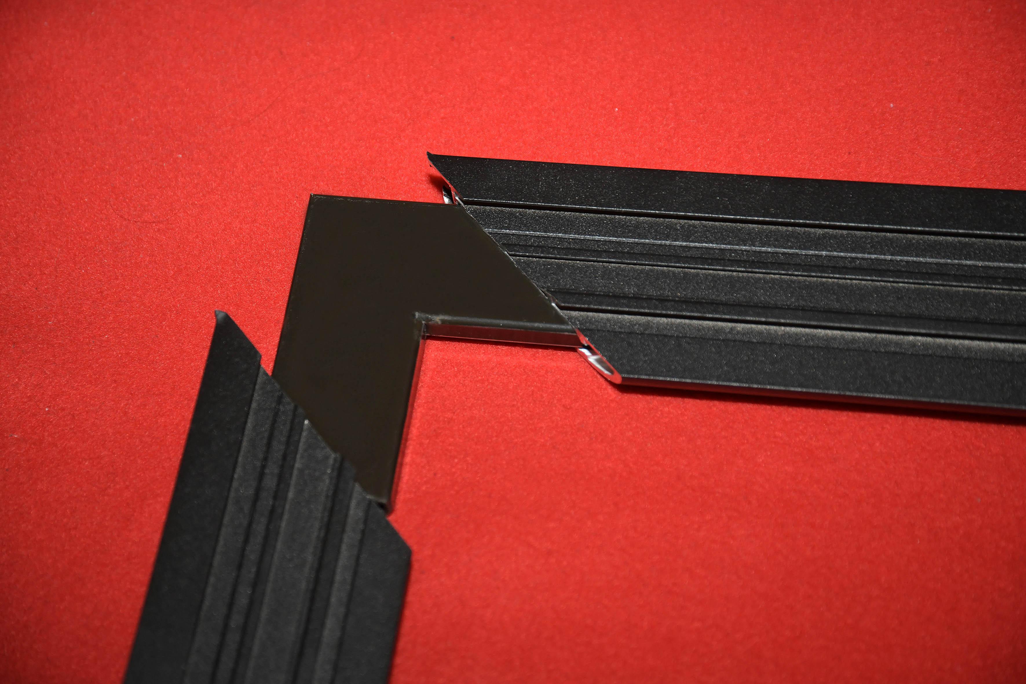 Nachdem die Wandhalter in die obere Schiene eingefügt sind, geht es weiter. Zum Lieferumfang gehören vier flache Winkel. Diese werden einfach in die Aluminium-Profile eingeschoben (Foto).